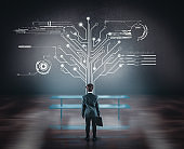 Businessman watching circuit board tree in the office. Network concept.