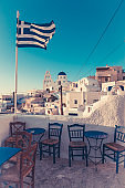 greece national flag over santorini island, greece