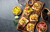 Toasts with mango, cream cheese, ham jamon serrano served on wooden board with red wine, gray slate background, top view. Copy space