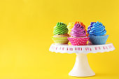 Tasty cupcakes on a yellow background