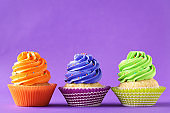 Tasty cupcakes on a purple background