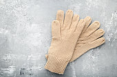 Knitted beige gloves on wooden table