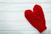 Knitted red gloves on wooden table