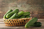 Fresh cucumbers in basket on grey wooden table