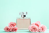 Perfume bottle with roses on mint background