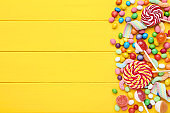 Sweet candies and lollipops on yellow wooden table