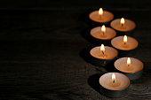 White burning candles on black background