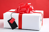 Black sale tag with gift box on red background