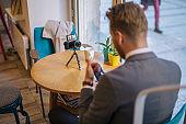Handsome influencer vlogging from a cafe