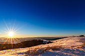 Sunset and stars at dusk in Carpathian mountain range.