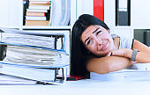 Young female office worker shocked by the huge amount of paper work. Deadline concepts