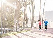 Joggers couple running outdoor in city track together - Sporty happy people training at morning in tropical place - Healthy lifestyle, happiness, jogging and vitality concept