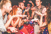 Happy friends dancing and throwing confetti with dj playing music in background - Young trendy people having party in night disco club - Nightlife and entertainment concept - Focus on disc jockey face