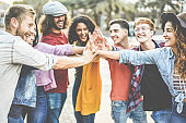 Young millennials friends stacking hands together - Happy students celebrating together - Youth lifestyle, university, social trends, relationship and friendship concept - Focus on hands