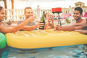 Happy friends cheering with champagne in pool party at sunset - Rich people having fun in tropical vacation outdoor - Holiday, youth lifestyle and friendship concept - Focus on center guys faces