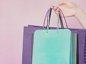 business ,finance and shopping concept from beauty woman hand hold group of pastel paper shopping bag by right hand with pink pastel isolated background