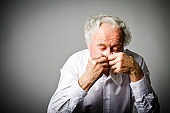 man in white is sneezing. Runny nose.