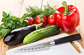 Different fresh vegetables, dill and parsley, cutting board and knife