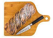 Bun with poppy and sugar powder, knife on cutting board