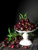 Fresh cherries in a decorative stand, on a dark wooden background with copy space. The concept of summer and harvest. Cherry Macro. Vegan, vegetarian, raw food