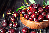 Fresh sweet cherries in plate on dark wooden background with copy space. Summer and harvest concept. Cherry macro. Vegan, vegetarian, raw food.