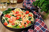 Pasta with fried prawns, peas, tomatoes and spinach in a frying pan, on a table with cider glasses.