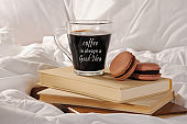 Morning cup of coffee with chocolate cakes Macaroons, on a pile of books in bed. Coffee is always a Good idea.