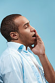 Sad Afro-American man is having toothache. against blue background