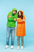 The young couplel posing at studio in autumn jackets isolated on blue