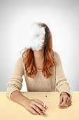 Tranquil woman sitting and smoking resting at the table. Cloud of smoke covering her face. Copy space