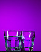 The water in two glassese on lilac background