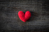 Alone handmade red heart  on wooden background. Heart broken, Love and Valentines day concept.