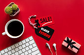Black Friday Sale text on a red and black tag with coffee cup, keyboard computer and gift box on red background. Shopping concept.