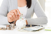 Woman hand putting America dollars banknotes money into piggy bank with stack of coins and alarm clock. Saving money wealth and financial concept.