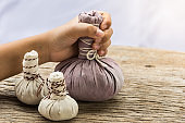 hand holding compress ball with wooden table