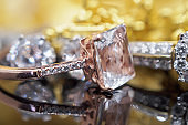 Luxury gold Jewelry diamond and pink topaz rings with reflection on black background