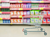 detergent shelves in supermarket or grocery store with empty shopping cart