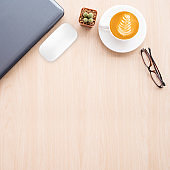 Office table with laptop, mouse, coffee cup on table background.