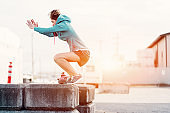 Woman doing high jumps in industrial city zone