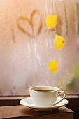 Cup of autumn tea (coffee, chocolate) and yellow leaves on rainy window, copy space. Hot drink for autumn mood.