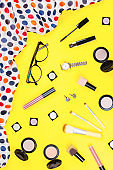 Fashion accessories, makeup products, jewelry and handbag on yellow background. Beauty and fashion concept, flat lay