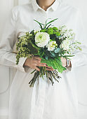 Young woman wearing white clothes holding bouquet. Flower shop concept