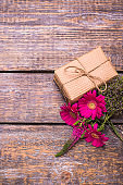 A box with a gift, a bouquet of red flowers on a wooden old background