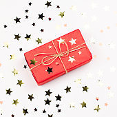 Red giftbox with golden Christmas decorations close up