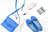 Female summer fashion accessories flat lay with flats, purse, sunglasses and cosmetics.