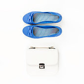 Female summer fashion accessories flat lay with blue flats and white purse