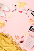 Autumn female clothes collection. Women fall fashion concept flat lay. Pink purse, pumps, scarf and cosmetics overhead