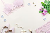 Woman elegant pink lace bra and panties, pumps and jewelry. Stylish lingerie flat lay.