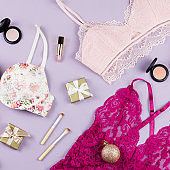 Different sets of lace lingerie, presents and Christmas decoration on pastel background. Woman fashion Christmas concept