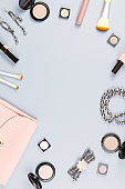 Fashion accessories, makeup products, jewelry and handbag on pastel background. Beauty and fashion concept, flat lay